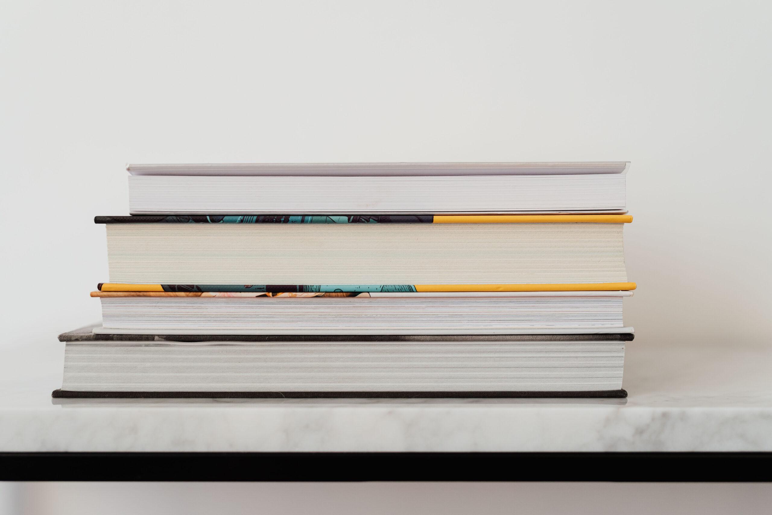 Böcker staplade på ett marmorbord.